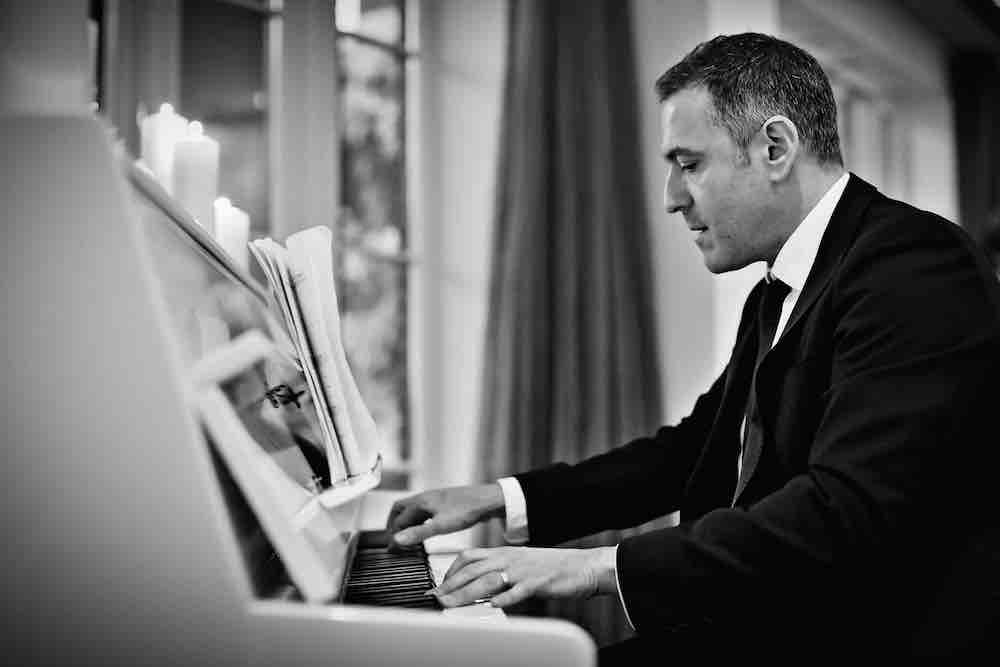 bryan-playing-on-white-upright-piano-at-candle-lit-drinks-reception